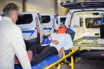 doctor transporting a man to the ambulance