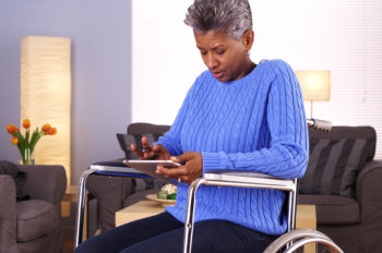 senior woman on a wheelchair with a tablet